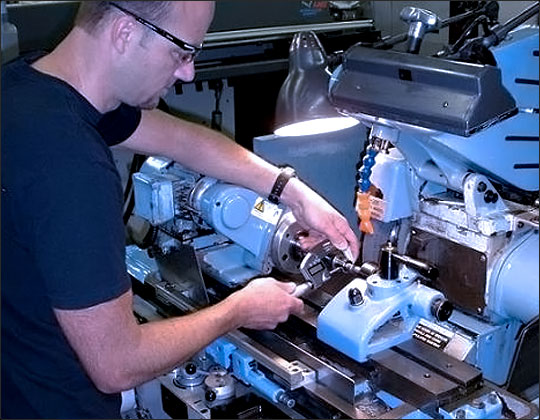 An employee running a grinding lathe in the Habco Tool & Development factory