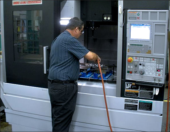 An employee cleaning a part in a CNC Mill at Habco Tool & Development
