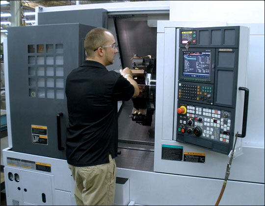An employee running a CNC lathe in the Habco Tool & Development factory